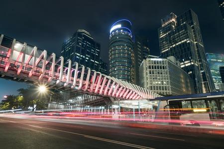 Jakarta, Indonesien. 05. März 2019: Schöne Nachtansicht der Sudirman Street mit futuristischer Fußgängerbrücke und Lichtwegen