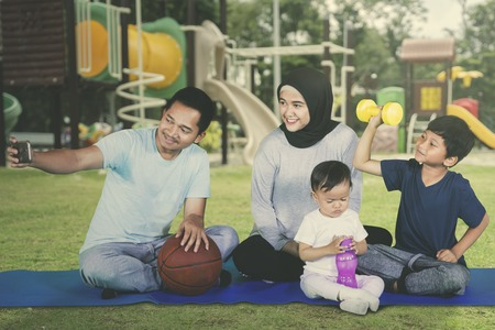 Happy family sitting at the playground and taking selfie photo together after exercising