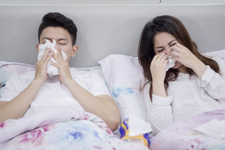 Sick Asian couple suffering influenza while lying together in the bedroom