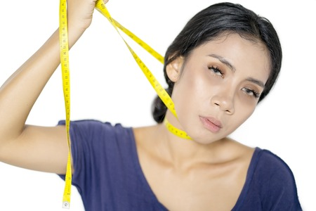 Diet concept. Frustrated woman strangling her neck with a measure tape, isolated on white background
