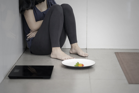 Close up of unknown woman suffering anorexia while sitting with a plate of salad and weight scales in the bathroom