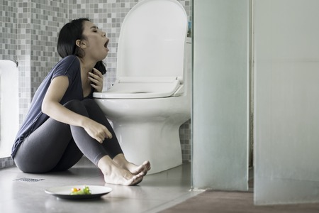 Eating disorder concept. Skinny woman vomiting after eating a plate of salad in the bathroom