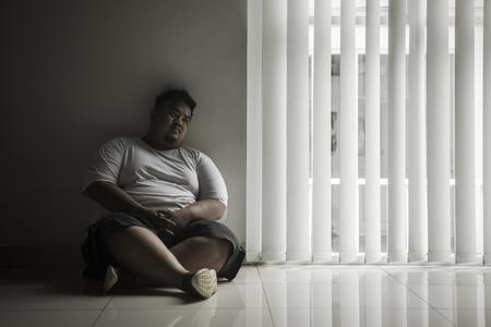 L'immagine di un uomo grasso solitario sembra un sogno ad occhi aperti mentre è seduto vicino alla finestra nella stanza buia