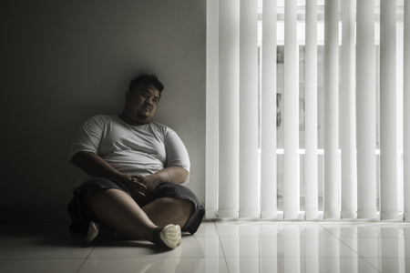 Picture of lonely fat man looks daydream while sitting near the window in the dark room 스톡 콘텐츠