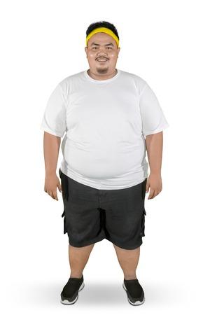 Longitud total de hombre gordo feliz vistiendo ropa deportiva mientras está de pie en el estudio, aislado sobre fondo blanco. Foto de archivo