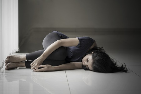 Diet concept. Skinny woman looks sad while lying on the floor in black background