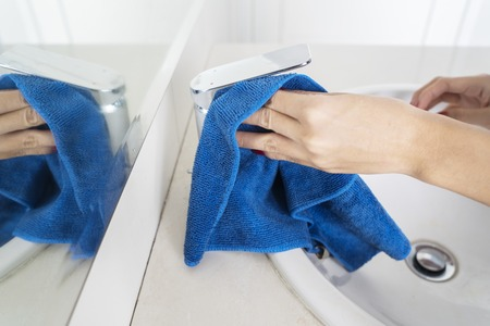 Close up of housemaid hands cleaning a faucet by using rag in the bathroom. Shot at home