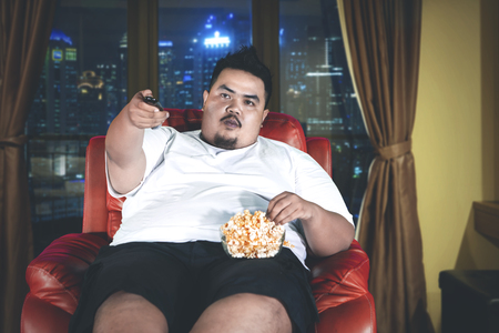 Picture of Asian fat man eating popcorn on the sofa while watching television in the apartment Imagens