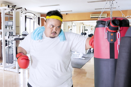Picture of fat man wearing sportswear while punching a boxing sack in the gym center