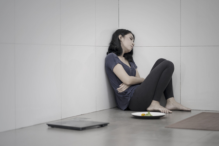 Young woman suffering anorexia while sitting with a plate of salad and weight scales in the bathroom Фото со стока