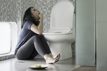 Picture of a young woman forcing herself to vomit with her fingers after eating in the bathroom. Eating disorder concept