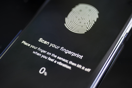 Close up of a smartphone displaying fingerprint id scan to unlock and lock screen. Shot over the table Editorial