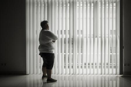 Foto van een eenzame man die uit het raam kijkt terwijl hij in de donkere kamer staat