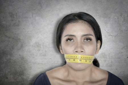 Picture of unhealthy woman covering her mouth with a measure tape. Diet concept