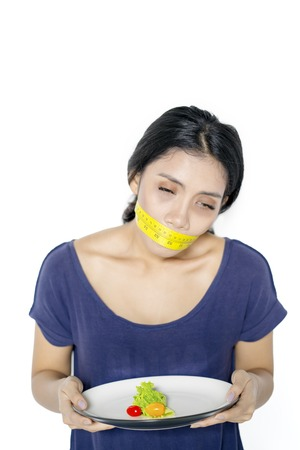 Portrait of a starving woman looks tired while holding a plate of salad and covering her mouth with a measure tape in the studio Banco de Imagens