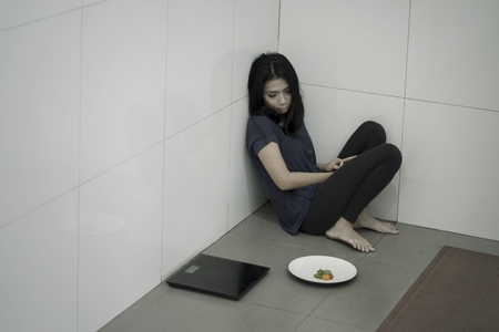 Picture of a skinny anorexic woman sitting with a plate of salad and weight scales in the bathroom. Weight loss concept