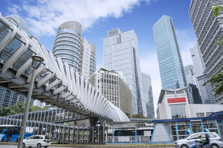 JAKARTA - Indonesia. March 25, 2019: Modern pedestrian bridge with skyscrapers under blue sky in Jakarta city