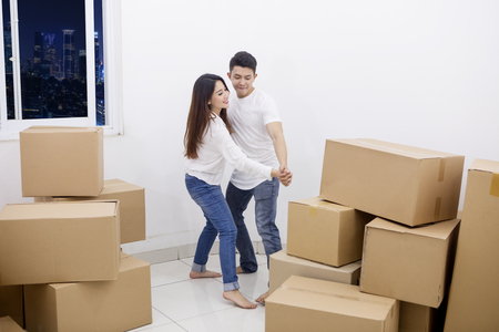 Image of a young couple dancing after moving into their new apartment with piles of cardboard boxes