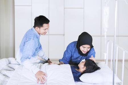 Imagen de padres jóvenes cuidando a su hijo enfermo durante una visita en la habitación del hospital