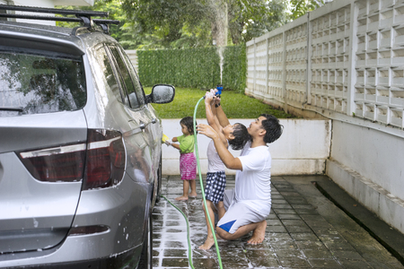 Young Asian father washing a car with his children at home while using a water hose and sponge