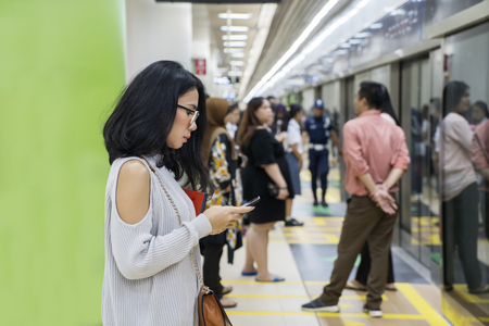 : Young woman using a mobile phone while waiting Jakarta train arrival in station