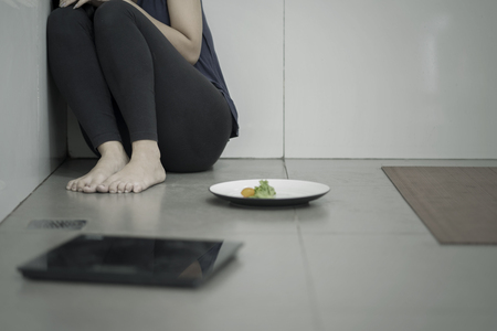 Portrait of lonely woman sitting with a plate of salad and weight scales in the bathroom. Weight loss concept