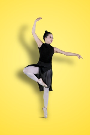 Full length of beautiful ballerina standing with tiptoe poses in the studio with yellow background