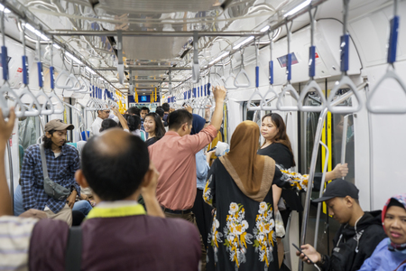 JAKARTA, Indonesia - March 27, 2019: Crowd passengers standing inside Jakarta MRT while holding handgrip
