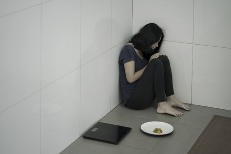 Asian anorexic woman sitting alone with a plate of salad in the bathroom. Eating disorder concept Stock Photo