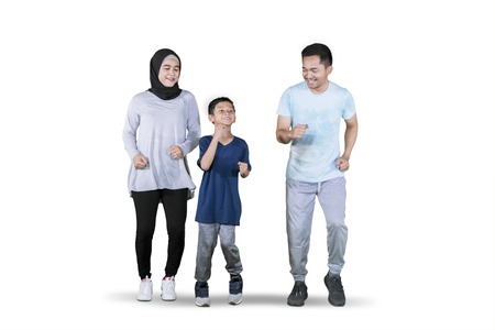Picture of young Asian family looks happy while doing exercise run in the studio, isolated on white background 写真素材