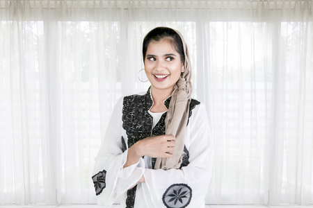 Picture of beautiful woman wearing Muslim clothes while standing at home