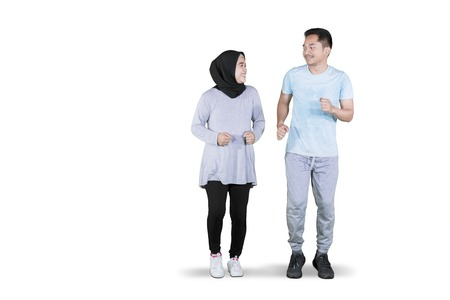 Picture of Muslim couple looks happy while jogging together in the studio, isolated on white background