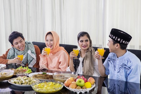 Group of Muslim people enjoying orange juice during break the fast together in the dining room. Shot at home