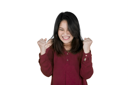 Picture of young Asian woman gritting her teeth while expressing furious in the studio, isolated on white background