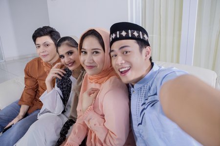Four cheerful Muslim people taking photo together during Eid Mubarak celebration. Shot at home 免版税图像