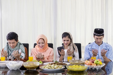 Group of young Muslim people praying together before break the fast in the dining room Stock Photo