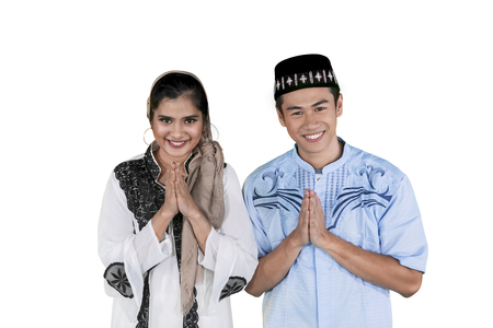 Muslim happy couple giving greeting hands at the camera while celebrating Eid Mubarak in the studio