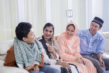 Picture of four Muslim people talking each other while sitting together on the couch. Shot at home