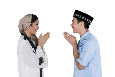 Muslim couple giving a greeting hand to forgive each other while celebrating Eid Mubarak in the studio
