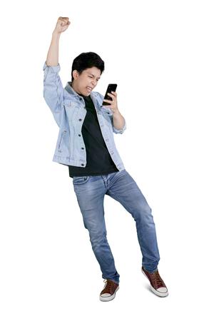 Pełna długość młodego, szczęśliwego mężczyzny trzymającego telefon komórkowy podczas świętowania swojego sukcesu w studio Zdjęcie Seryjne