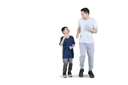 Picture of young father doing exercise run with his son in the studio, isolated on white background