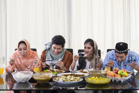 Group of young people eating together during Eid Mubarak celebration in the dining room. Shot at home