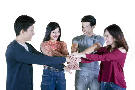 Group of four college students joining hands together in a circle, isolated on white background