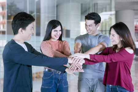 Group of four college students joining hands together in a circle with happy expression