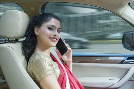 Picture of happy Indian woman wearing sari clothes in a car while talking on a phone