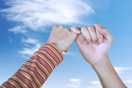 Close up of couple hands make a pinkie promise with blue sky background