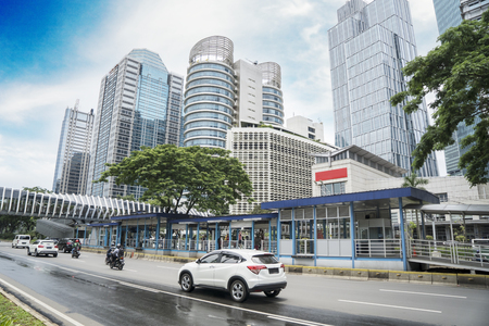 Image of vehicles passing through Sudirman street with bus shelter and pedestrian bridge in Jakarta city 스톡 콘텐츠