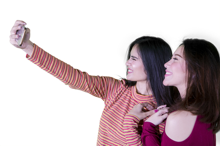 Close up of two happy women using a smartphone to take a selfie photo together, isolated on white background