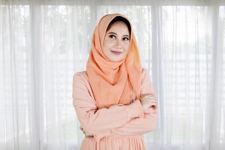 Porträt des muslimischen hübschen Mädchens faltete ihre Hände, während sie zu Hause stand Standard-Bild