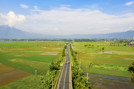 Aerial view of beautiful trans-Java Toll Road in middle of farmland at sunny day in Semarang, Indonesia